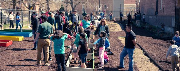 Zoo staff, adults, and children build a community garden
