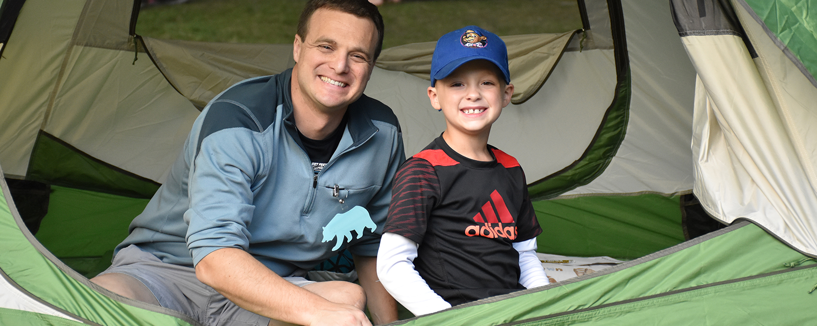 Father and son getting ready to camp in their tent